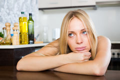 Sad young woman sitting at kitchen. Sad lonely young woman sitting in the kitchen at home Royalty Free Stock Photo