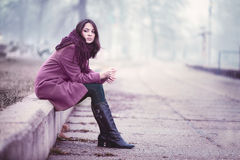 Sad Young Woman Sitting Outdoors. Disappointing Young Woman is Sitting in Depression on the Stone Parapet in the Gloomy Autumn Day Stock Image