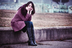 Sad Young Woman Sitting Outdoors. Disappointing Young Woman is Sitting in Depression on the Stone Parapet in the Gloomy Autumn Day Stock Photos