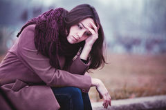 Sad Young Woman Sitting Outdoors. Disappointing Young Woman is Sitting in Depression on the Stone Parapet in the Gloomy Autumn Day Stock Images