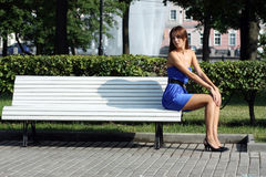 Sad young woman sitting on a park bench Stock Photos