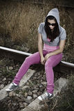 Sad, young woman sitting on the railroad Stock Image