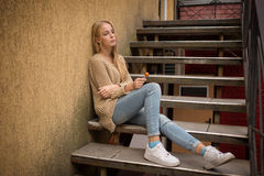 Sad young woman. Sitting on steps royalty free stock photo