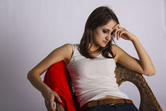 Sad young woman sitting on straw chair Royalty Free Stock Images