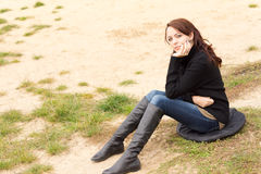 Sad young woman sitting thinking. Sad young woman sitting on a cushion on sandy ground thinking with her chin resting on her hand as she stares into the distance Stock Photo