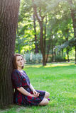 Sad young woman sitting under a tree Royalty Free Stock Images