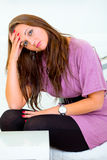 Sad young woman sitting on white couch Stock Image