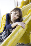 Sad young woman sitting on yellow bench Royalty Free Stock Photography