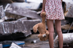 Sad young woman standing and holding her bear doll in her left hand Royalty Free Stock Photography
