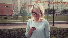 Sad young woman standing in the park area among buldings using her smartphone texting feeling sad stock video