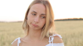 A sad young woman stands in a field and looks into the camera stock video