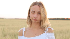 A sad young woman stands in a field and looks into the camera stock video footage