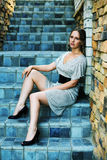 Sad young woman on the steps. Sad young woman sitting on the stairs against stone wall Royalty Free Stock Photos