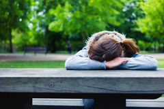 Sad young woman at table in park Stock Photography