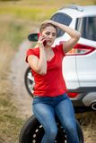 Sad young woman talking with car service by mobile phone in field stock photo