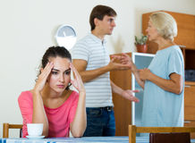 Sad young woman watching husband and mother having fight. Upset girl apart from her husband and senior mother quarrelling Royalty Free Stock Images