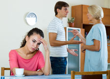 Sad young woman watching husband and mother having fight. Upset girl apart from her husband and senior mother quarrelling Royalty Free Stock Photo
