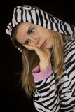 Sad young woman wearing black and white striped cat pajamas Royalty Free Stock Photo