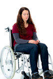 Sad young woman in wheelchair. In front of white background Stock Photos