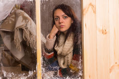 Sad young woman in a winter cabin royalty free stock photography
