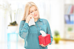 Sad young woman wiping her eyes at home Royalty Free Stock Photo