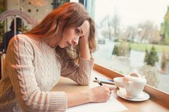Sad young woman writing letter with broken heart stock photo