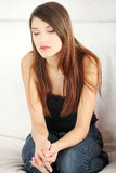 Sad young wowan's sitting on couch. Royalty Free Stock Photos