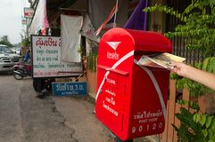 Put the postcards to the mailbox in Thailand. Sadao, Thailand - June, 2015: Traveler sending postcards to friends during travel in Asia. Put the cards to the stock photo