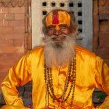 Saddhu z szafranową żółtą silky koszula, Pashupatinath świątynia obrazy royalty free