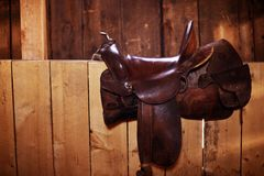 Saddle. Brown Leather Saddle - Western Style Saddle on the Wood Fence. Horizontal Photo Stock Image