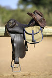 Saddle bag and hat. A vertical photograph of horse riding tack, including saddle, bag and leather hat Stock Images