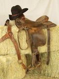 Saddle & Hat. Saddle and hat resting in hay bales Royalty Free Stock Photos