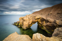 Saddle Rocks in smooth water Stock Images