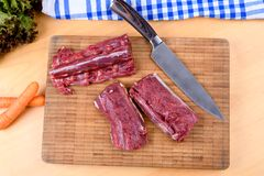 Saddle of venison on wooden board Stock Images