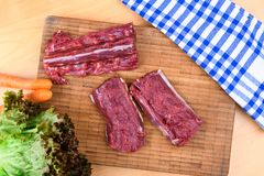 Saddle of venison on wooden board Stock Photos