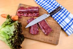 Saddle of venison on wooden board Royalty Free Stock Photos