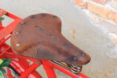 Saddle Vintage Red bicycle Closeup, old brick wall background Stock Photography