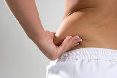 Saddlebag Flab. Young woman pinches the fat on the side of her waist to show the flab Stock Photography