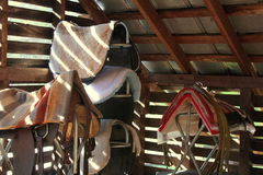 Saddles in the barn. Saddles at the ready in the bard royalty free stock photos