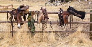 Saddles on Fence. Saddles on a rail fence waiting to be used on horses Royalty Free Stock Photo