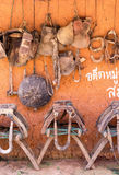 Saddles and horse gear. Traditional Chinese Asian wooden mule saddles lined up and other leather horse gear hanging on an orange wall Stock Image