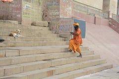 sadhu descending steps on ghat in varanasi uttar pradesh India