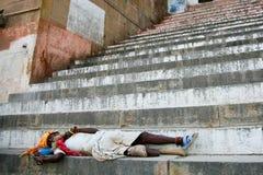 Sadhu equipado com pernas que dorme nas escadas de um ghat, Índia Foto de Stock