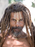 Sadhu, holy man sits on the ghat along the Ganges river. Rishikesh, India Stock Image