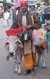 Sadhu met koe die aalmoes op de straat in Pushkar, India zoeken royalty-vrije stock afbeelding