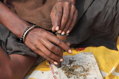 Sadhu is preparing his chillum to smoke ganja marihuana. ALLAHABAD, INDIA - FEBRUARY 07, 2013: Sadhu is preparing his chillum to smoke ganja marihuana Royalty Free Stock Photo