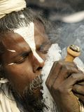 Sadhu, a saint enjoying marijuana in Shivaratri Festival Royalty Free Stock Photo