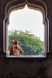 Sadhu sitting and playing the tumbi at window of Chaturbhuj Temple Stock Images
