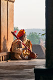Sadhu sitting and playing the tumbi at window of Chaturbhuj Temple Stock Photo
