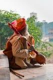 Sadhu sitting and playing the tumbi at window of Chaturbhuj Temple Royalty Free Stock Photography